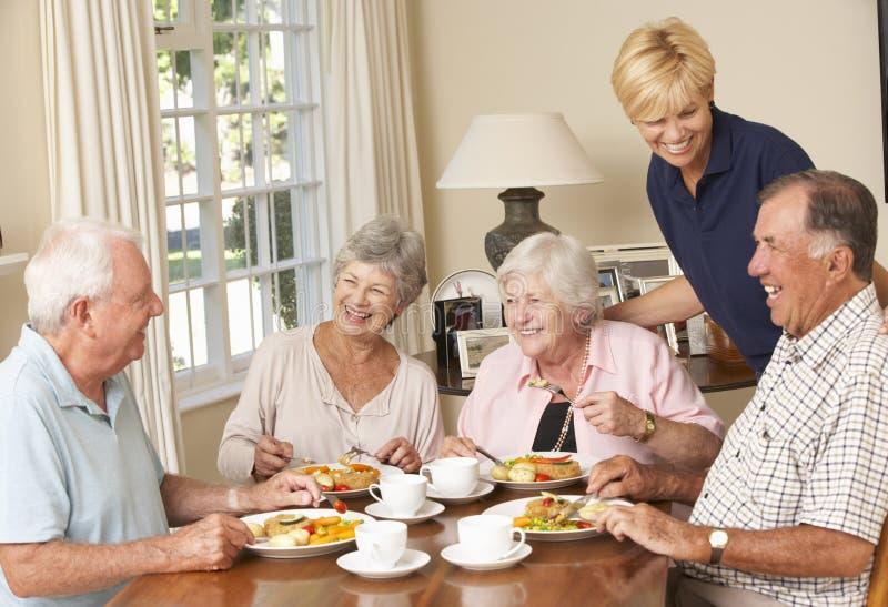 Gruppo di coppie senior che gode insieme del pasto nella casa di cura con fotografia stock