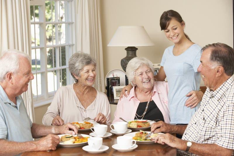 Gruppo di coppie senior che gode insieme del pasto nella casa di cura con l'assistente adolescente fotografie stock