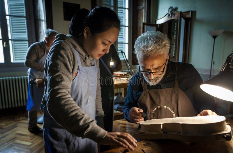 Gruppo di creatore del violino degli artigiani che lavora ad un nuovo violino fotografia stock libera da diritti