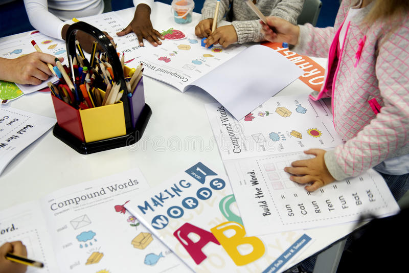 Gruppo di diversi studenti che colorano libro di esercizi nella classe immagini stock libere da diritti