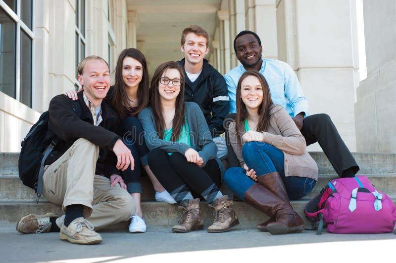 Gruppo di diversi studenti sulla città universitaria immagini stock