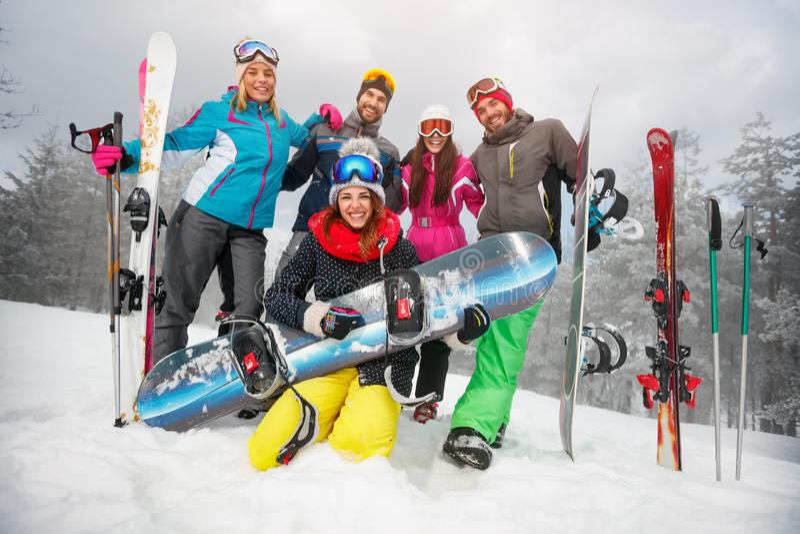 Gruppo di divertiresi felice degli amici Snowbarders e gruppo degli sciatori immagine stock