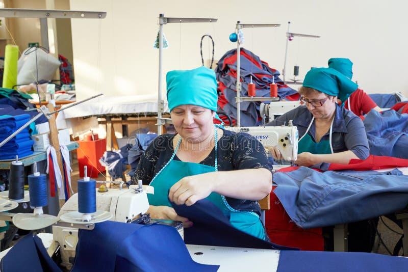 Gruppo di donne adulte, cucitrici alla fabbrica dell'indumento immagine stock
