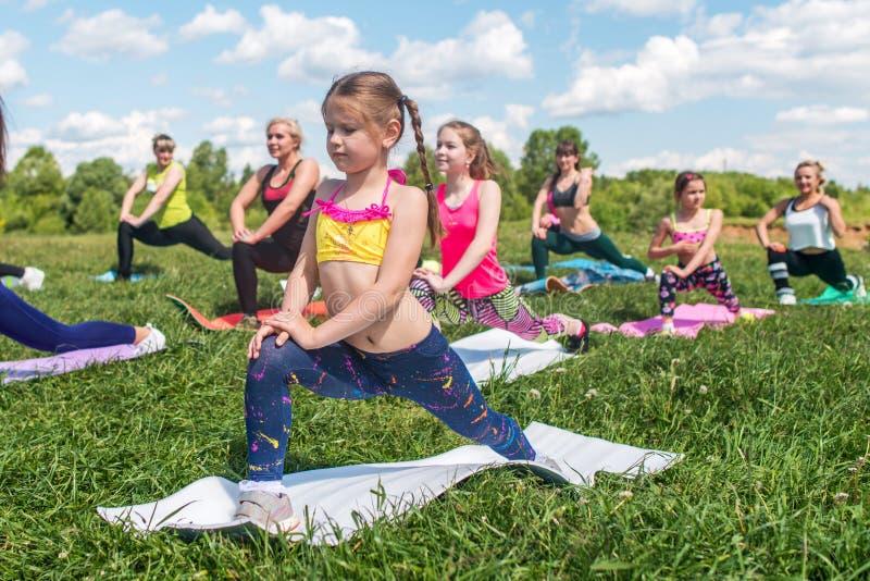 Gruppo di donne che esercitano e che fanno affondo al campo di addestramento immagini stock