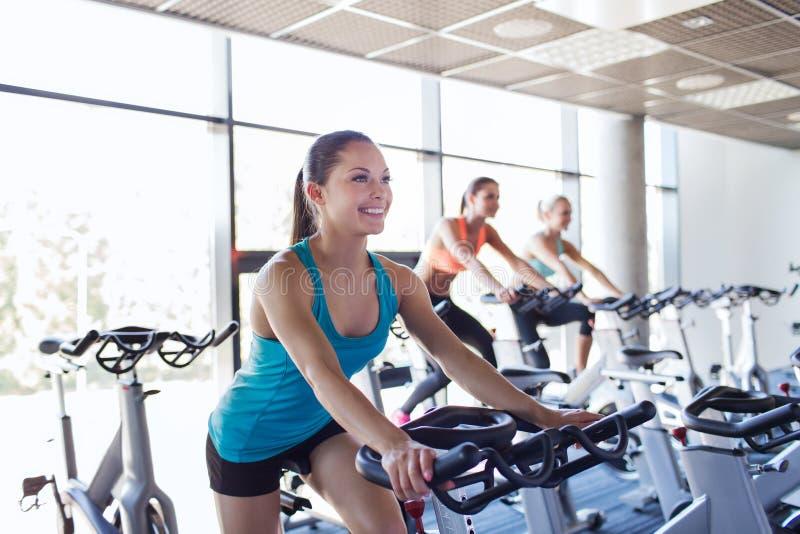 Gruppo di donne che guidano sulla bici di esercizio in palestra immagine stock libera da diritti