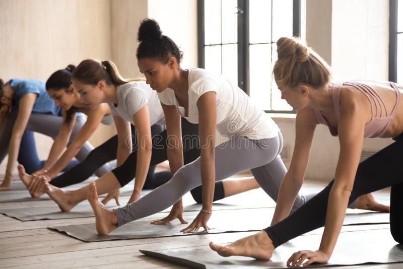 Gruppo di donne che praticano lezione di yoga, facente i mezzi exercis di spaccature fotografia stock libera da diritti
