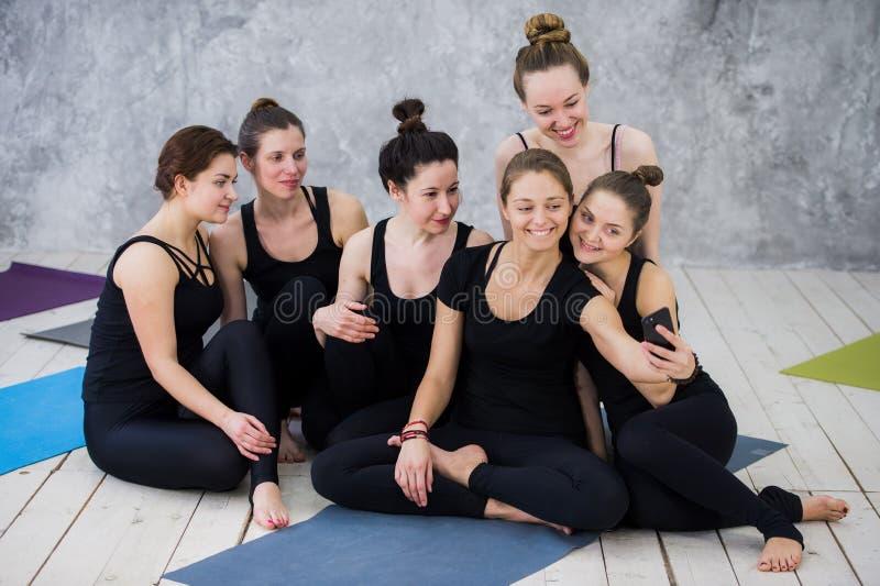 Gruppo di donne che si siedono e che si rilassano dopo una classe lunga di yoga e che prendono selfie fotografie stock