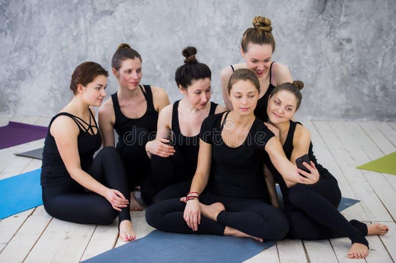 Gruppo di donne che si siedono e che si rilassano dopo una classe lunga di yoga e che prendono selfie immagine stock