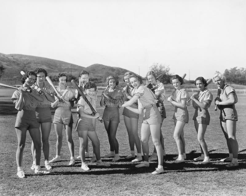Gruppo di donne che tengono le mazze da baseball e condizione in una fila (tutte le persone rappresentate non sono vivente più lu immagine stock