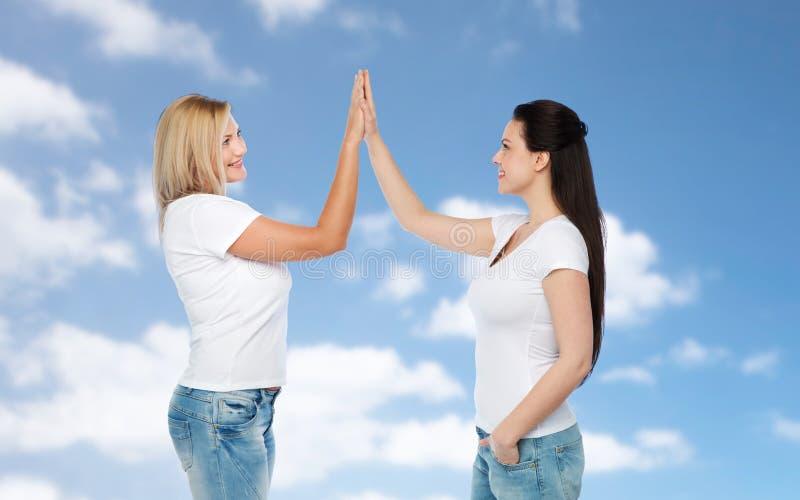Gruppo di donne differenti felici in magliette bianche fotografie stock