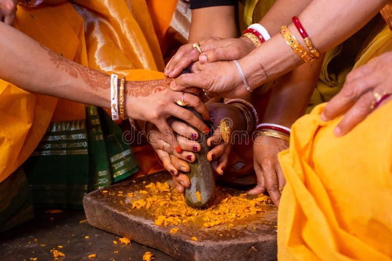 Gruppo di donne indiane che tengono una pace di pietra del mortaio per la fabbricazione della pasta della curcuma per cerimonia d fotografie stock libere da diritti