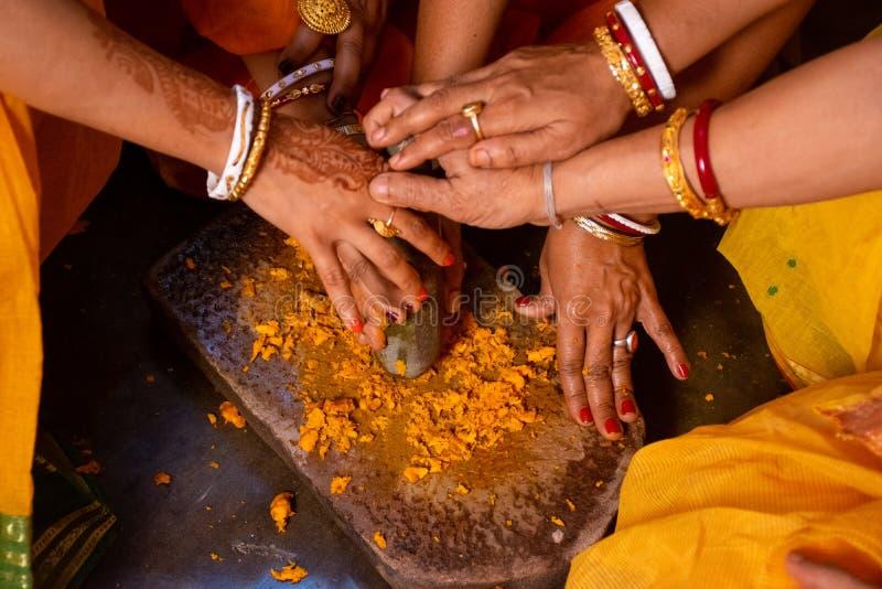 Gruppo di donne indiane che tengono una pace di pietra del mortaio per la fabbricazione della pasta della curcuma per cerimonia d fotografia stock libera da diritti