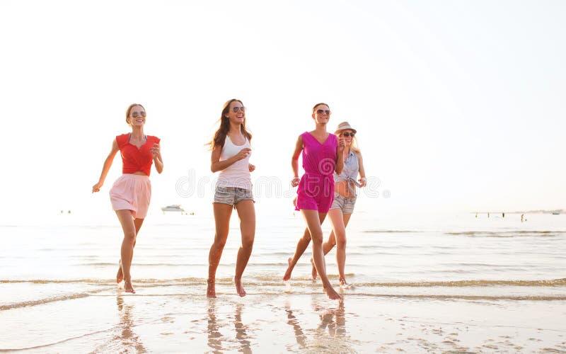 Gruppo di donne sorridenti che corrono sulla spiaggia fotografie stock