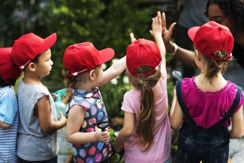 Gruppo di escursioni della scuola dei bambini che impara all'aperto smilin attivo fotografia stock