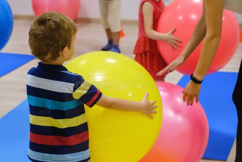 Gruppo di esercizio sportivo felice del ` s dei bambini con la palla, palestra di forma fisica fotografia stock libera da diritti