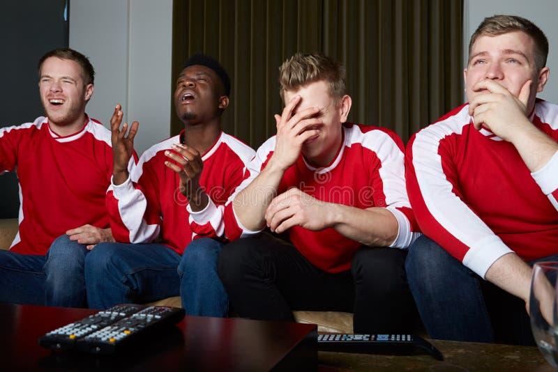 Gruppo di fan di sport che guarda gioco sulla TV a casa fotografia stock