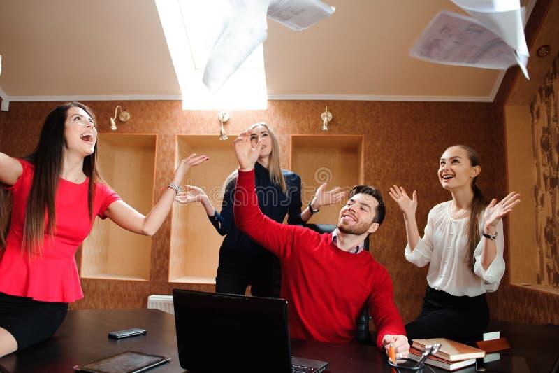 Gruppo di gente di affari che celebra gettando le loro carte d'ufficio nell'aria fotografia stock