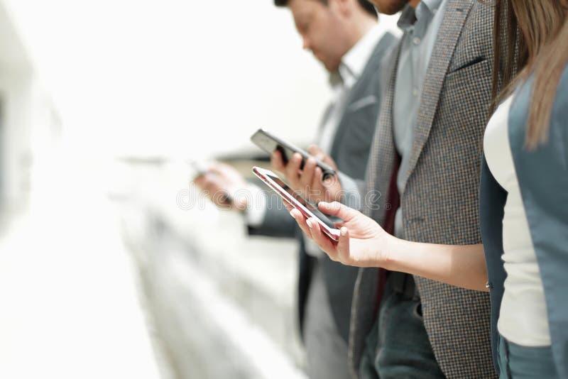 Gruppo di gente di affari che esamina gli schermi del loro smartph immagine stock libera da diritti