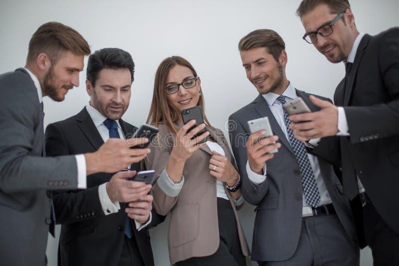 Gruppo di gente di affari che legge un messaggio sui telefoni fotografia stock libera da diritti
