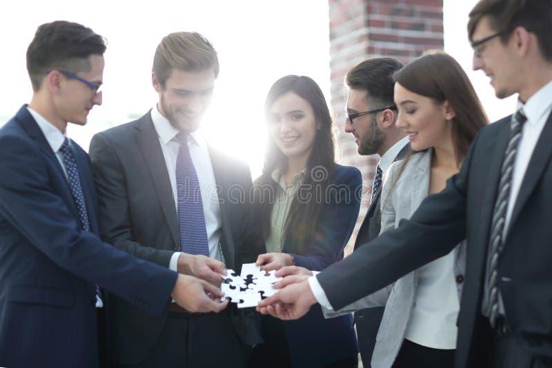 Gruppo di gente di affari che monta puzzle, supporto del gruppo immagine stock