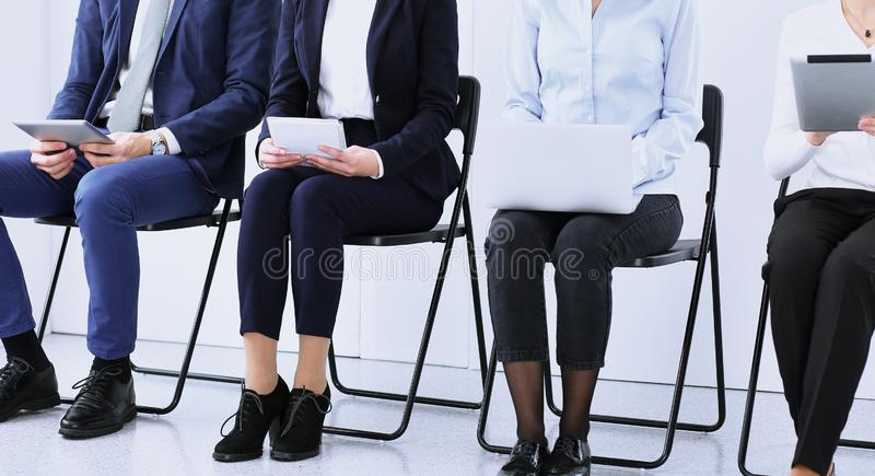 Gruppo di gente di affari che si siede nell'ufficio e nell'intervista di lavoro aspettante mentre facendo uso degli aggeggi, prim fotografia stock libera da diritti