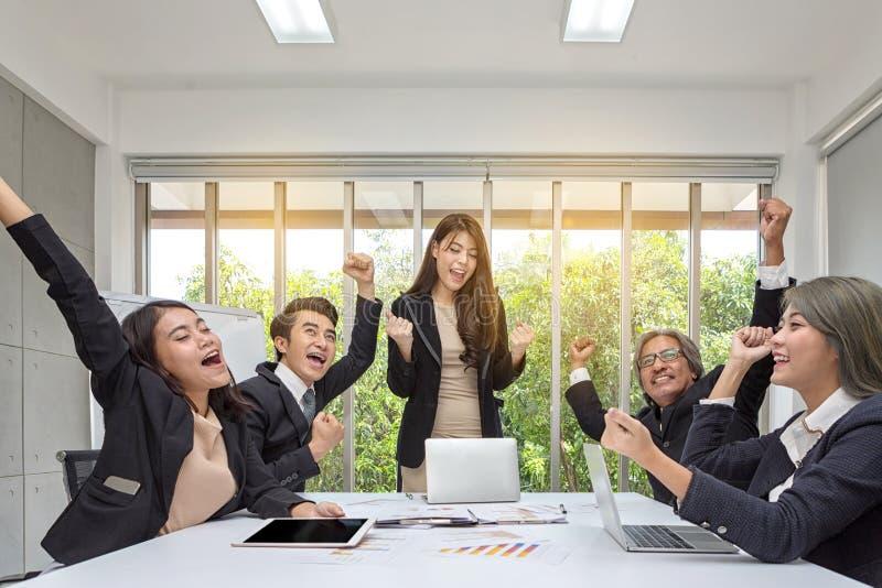 Gruppo di gente di affari felice che incoraggia nell'ufficio Celebri il successo Il gruppo di affari celebra un buon lavoro nell' immagine stock libera da diritti