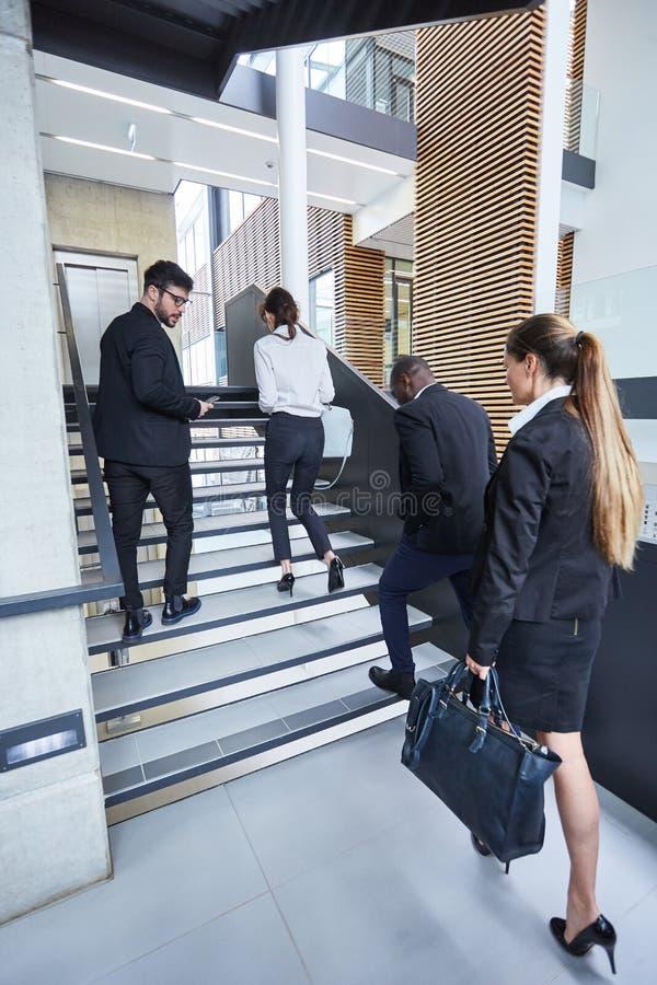 Gruppo di gente di affari nel pozzo delle scale fotografie stock