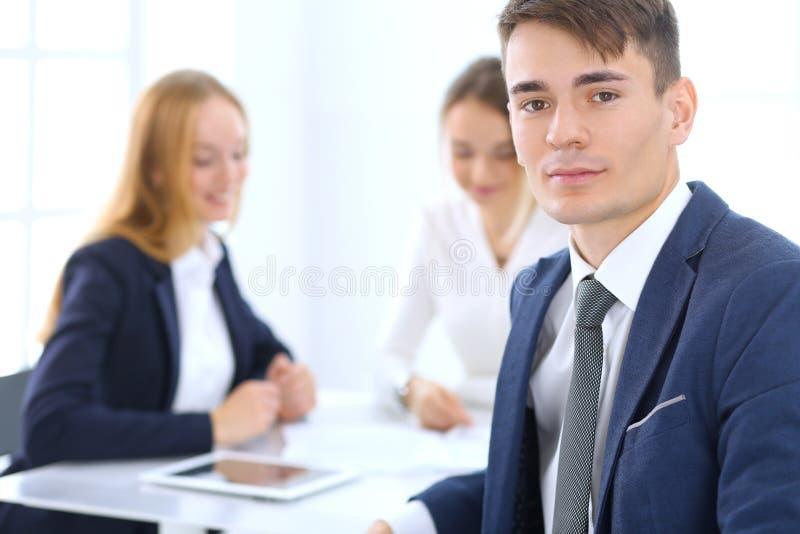 Gruppo di gente di affari o di avvocati che discute i termini della transazione nell'ufficio Fuoco al giovane uomo d'affari Riuni fotografia stock libera da diritti