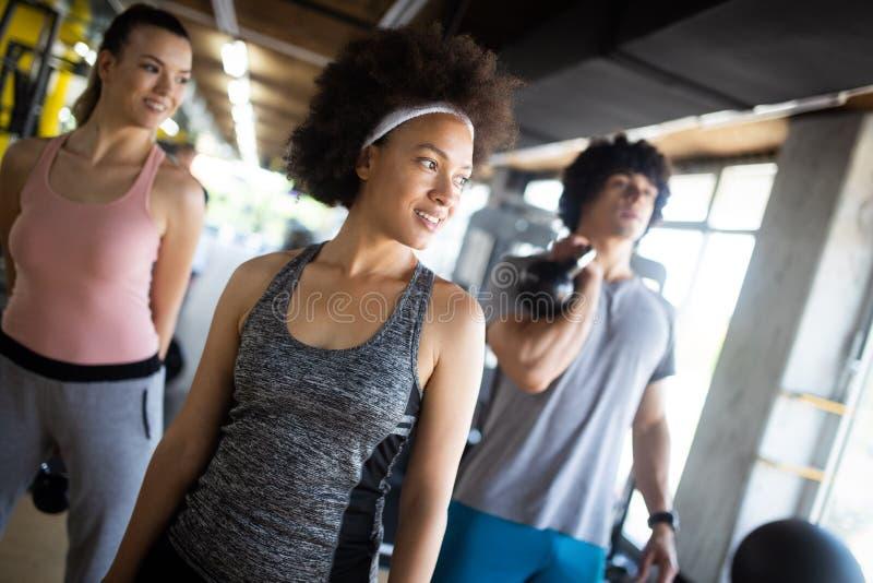 Gruppo di gente allegra in una palestra Concetti circa lo stile di vita e lo sport in un club di forma fisica fotografia stock libera da diritti