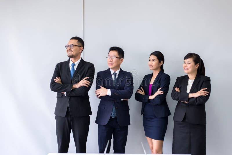 Gruppo di gente asiatica di affari che sta e che guarda con le armi trasversali dopo la riunione, presentazione di successo e sem fotografie stock