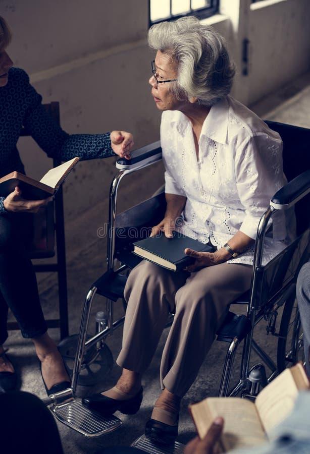 Gruppo di gente di Cristianità che legge insieme bibbia immagini stock