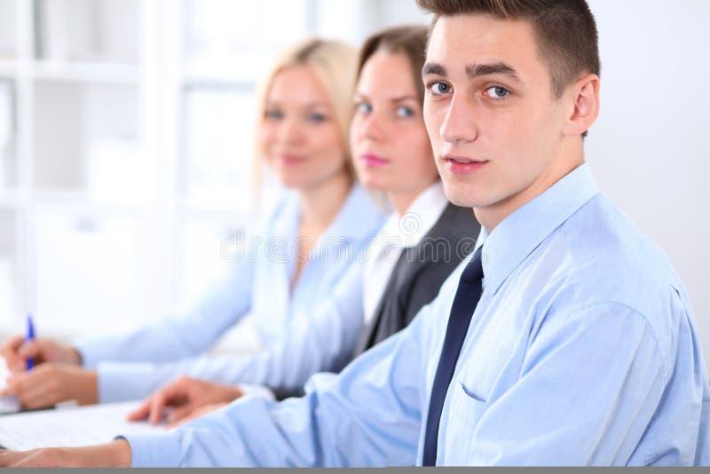Gruppo di gente di affari alla riunione sui precedenti dell'ufficio immagine stock libera da diritti