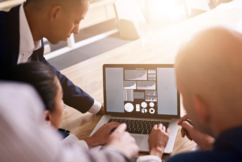 Gruppo di gente di affari che esamina i grafici su un computer portatile fotografia stock libera da diritti