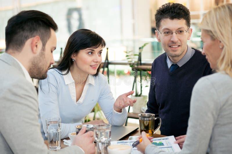 Gruppo di gente di affari che si incontra nella caffetteria e che tiene una b fotografie stock libere da diritti