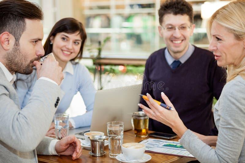 Gruppo di gente di affari che si incontra nella caffetteria e che tiene una b immagini stock
