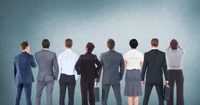 Gruppo di gente di affari che sta davanti al fondo blu in bianco immagine stock