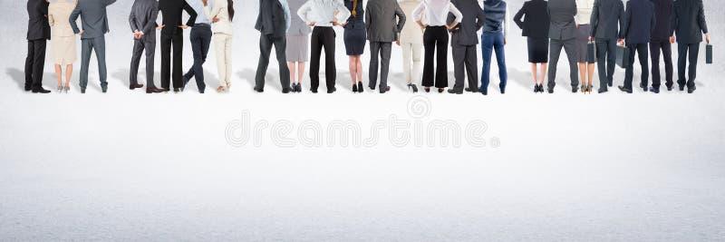 Gruppo di gente di affari che sta davanti al fondo grigio in bianco fotografia stock libera da diritti