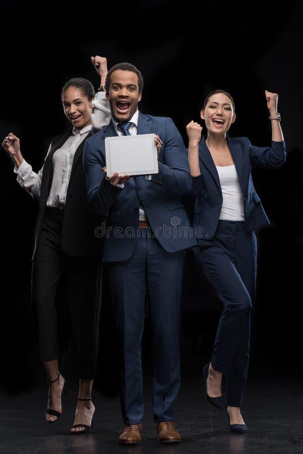 Gruppo di gente di affari che tiene compressa digitale e che celebra successo immagine stock