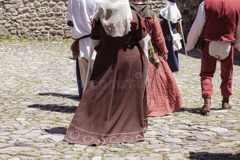 Gruppo di gente irriconoscibile vestita nella camminata medievale dei costumi immagini stock