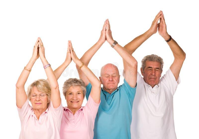 Gruppo di gente matura che fa yoga immagini stock libere da diritti