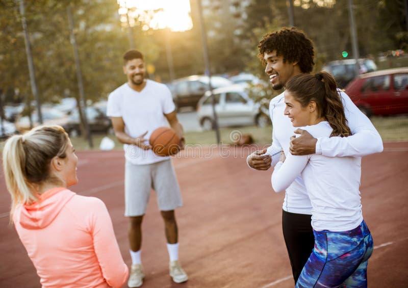 Gruppo di gente multietnica che gioca pallacanestro sulla corte fotografie stock