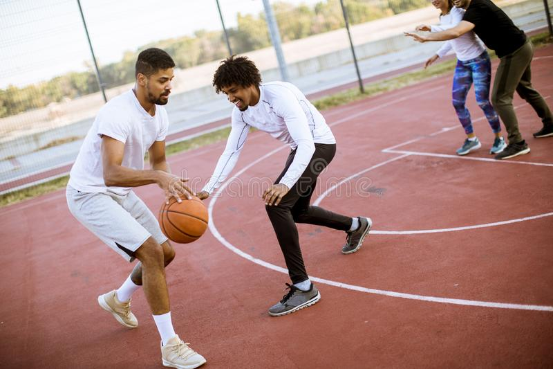 Gruppo di gente multietnica che gioca pallacanestro sulla corte immagini stock libere da diritti