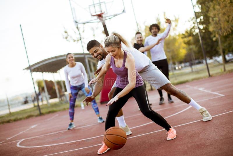 Gruppo di gente multietnica che gioca pallacanestro sulla corte immagini stock