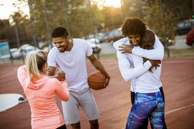 Gruppo di gente multietnica che gioca pallacanestro sulla corte immagine stock libera da diritti