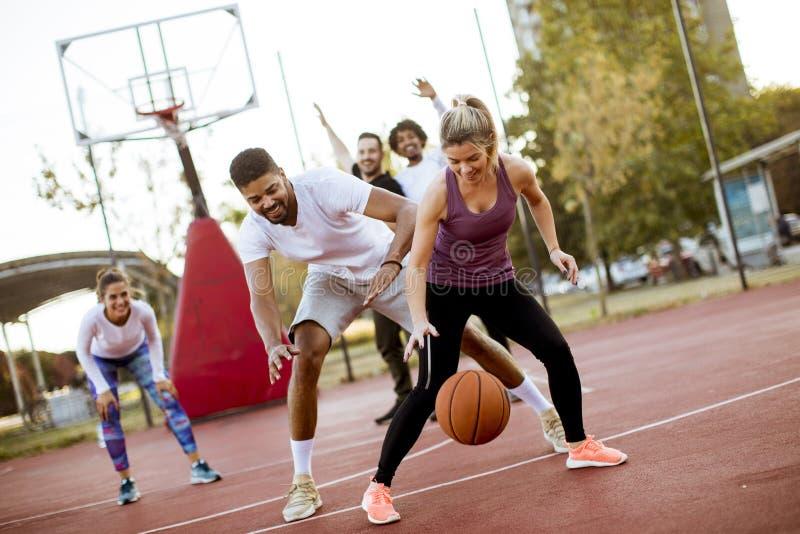 Gruppo di gente multietnica che gioca pallacanestro sulla corte fotografia stock libera da diritti