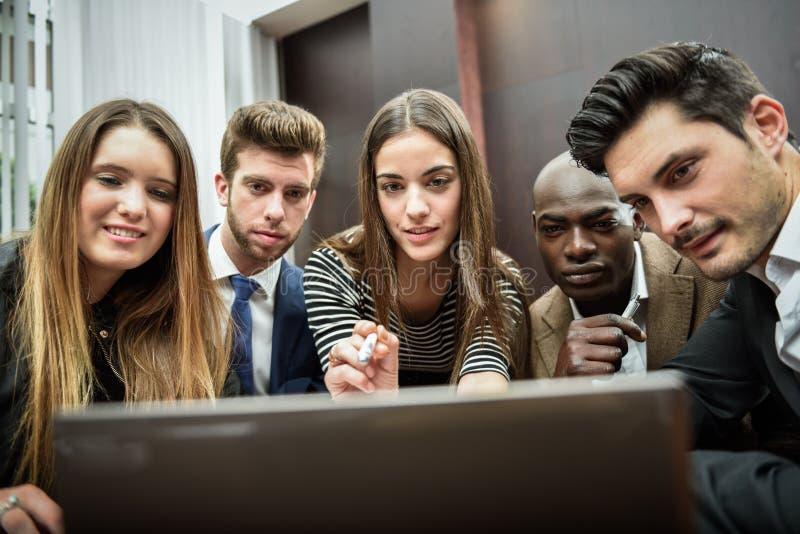 Gruppo di gente occupata multietnica che esamina un computer portatile immagini stock libere da diritti