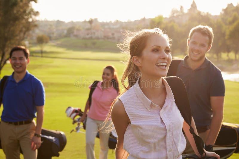 Gruppo di giocatori di golf che camminano lungo le borse di golf di trasporto del tratto navigabile fotografia stock libera da diritti