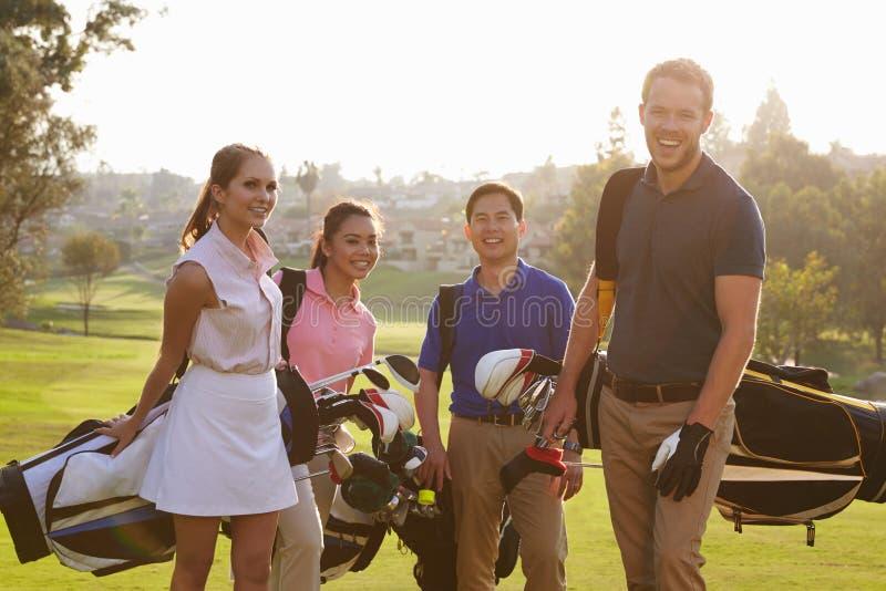 Gruppo di giocatori di golf che camminano lungo le borse di golf di trasporto del tratto navigabile fotografia stock