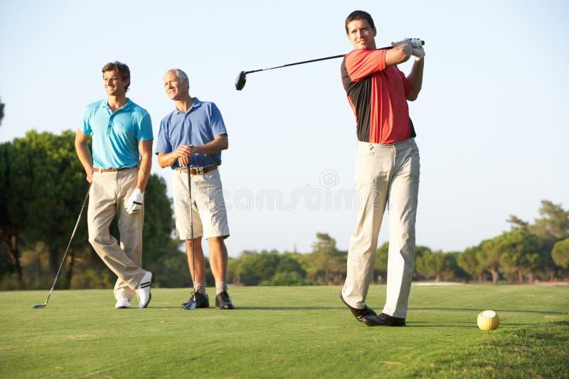 Gruppo di giocatori di golf maschii che un a Tire fuori fotografia stock libera da diritti