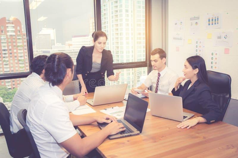 Gruppo di giovane gruppo di affari con la riunione diritta del capo del responsabile della donna nell'auditorium immagini stock